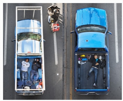 Aerial photograph of two pickup trucks with men lying flat in the back