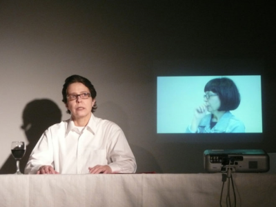 A photo of Johanna Houesholder speaking with a video image behind her