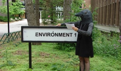 "Image from project poster featuring a bird-headed figure standing beside a sign which reads ""environment 1"""