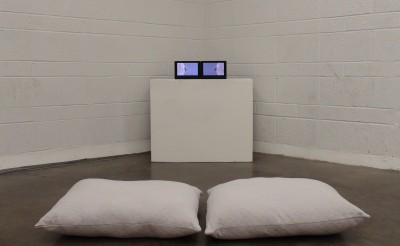 image of video screen on white plinth with two white pillows in the foreground