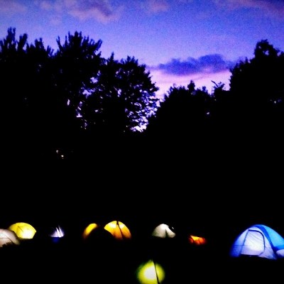 Photo of tents glowing at dusk