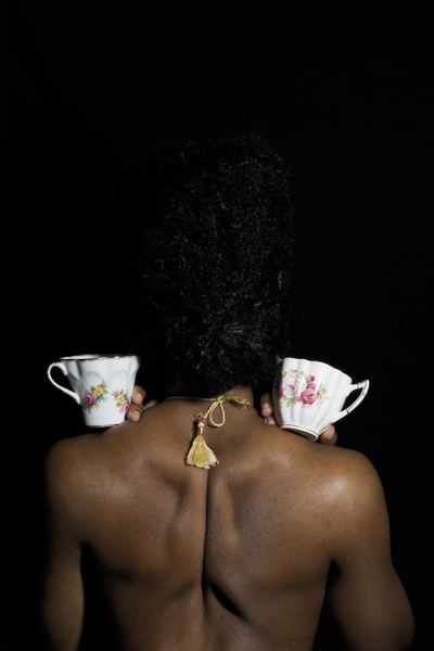 Photo of woman's back with teacups on her shoulders
