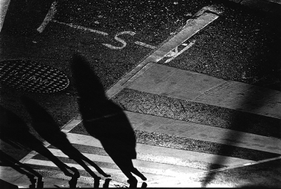black and white image of shadows crossing a street
