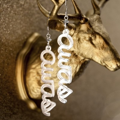 Pair of silver earrings hanging from a metallic sculpture of a mounted deer head