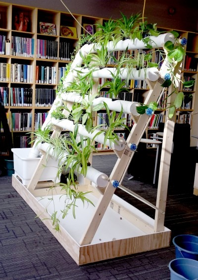 A photograph of a hydroponic garden system built from horizontal pipes on a wooden triangle frame, growing with lush plants