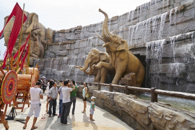 Group of tourists stopping to look at life-size elephant sculptures protruding out of a stone water feature