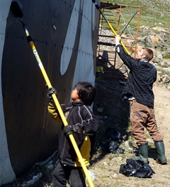 Patrick Thompson and Gootileak Echo paint a mural in Iqaluit. Image courtesy Cape Dorset Mural Project