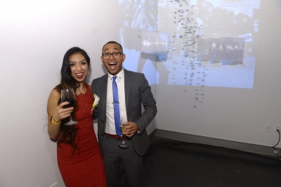 Woman poses with man in front of a video projection