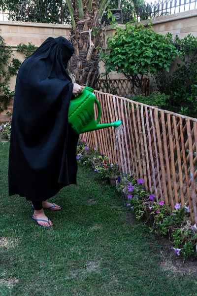 photo of individual wearing a burka and watering a flowerbed