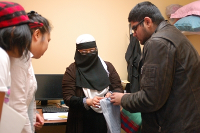 Sewing collective member shows fabric to students