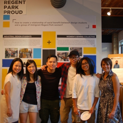 Group of six students and faculty in front of display