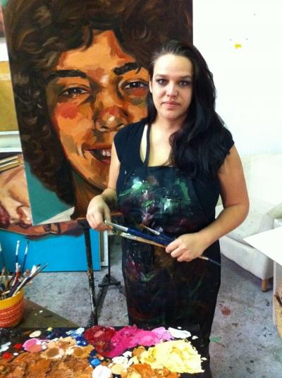 Photo of Ilene Sova with artwork in the background
