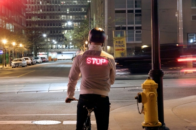 "A cyclist photographed from behind with digitally lit shirt that reads ""stop"""