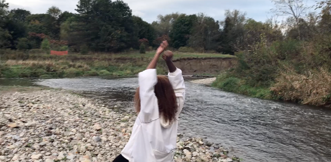 A person with long hair facing a river with their arms raised above their head,