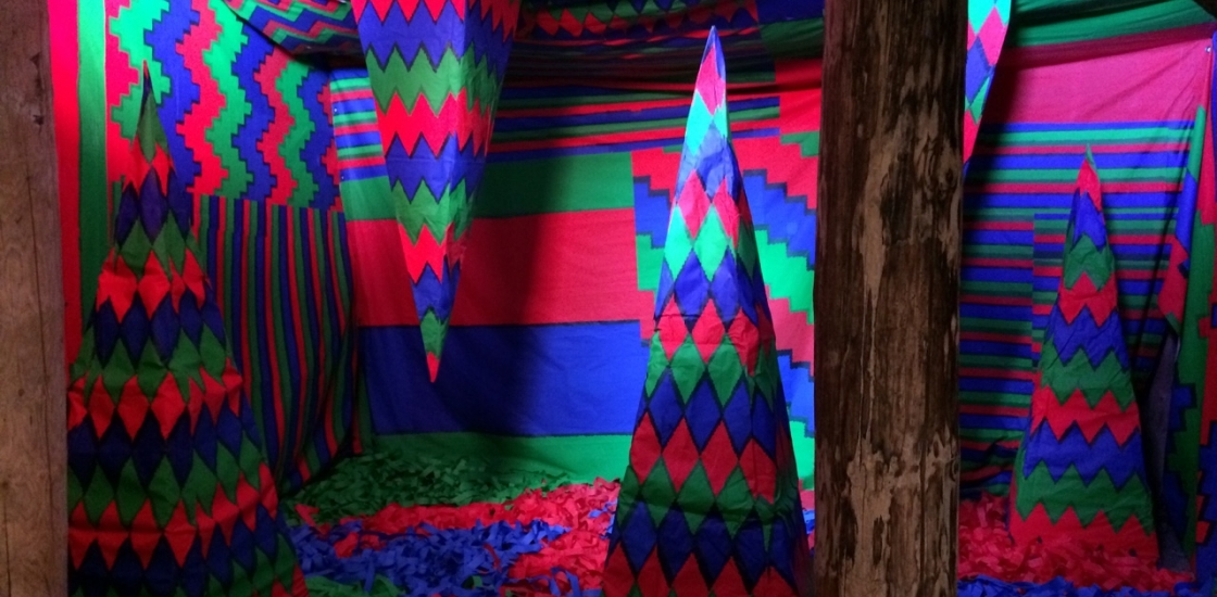 brightly coloured geometic shapes in a cave like setting