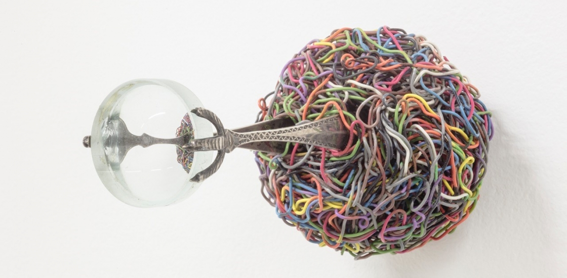 a ball of tagled colourful wires, a metal object and a glass sphere
