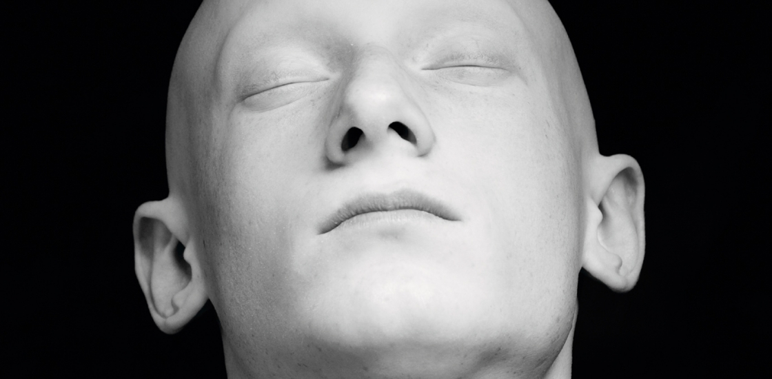 Black and white photograph of a bald human head with eyes closed