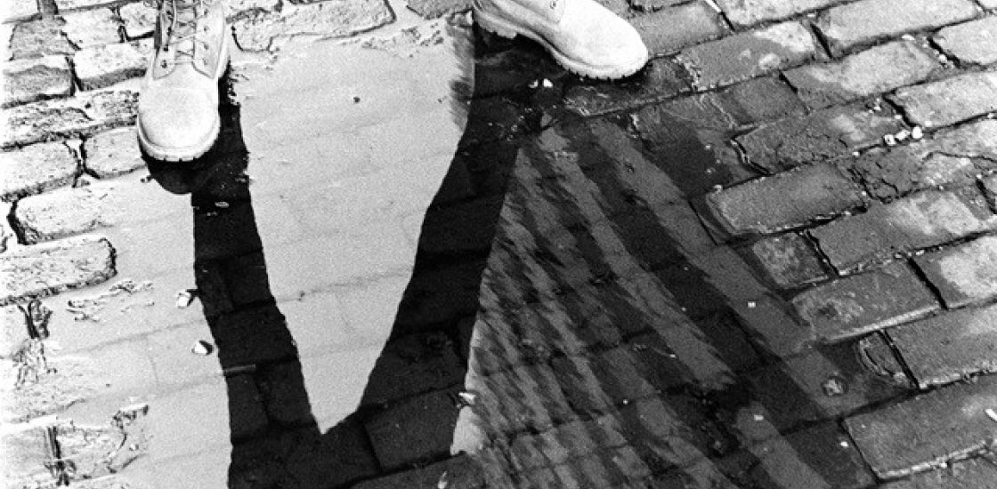 Black and white photo of legs straddling a puddle