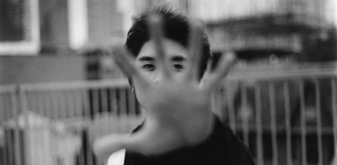 black and white photo of a young man with a raised hand in front of face