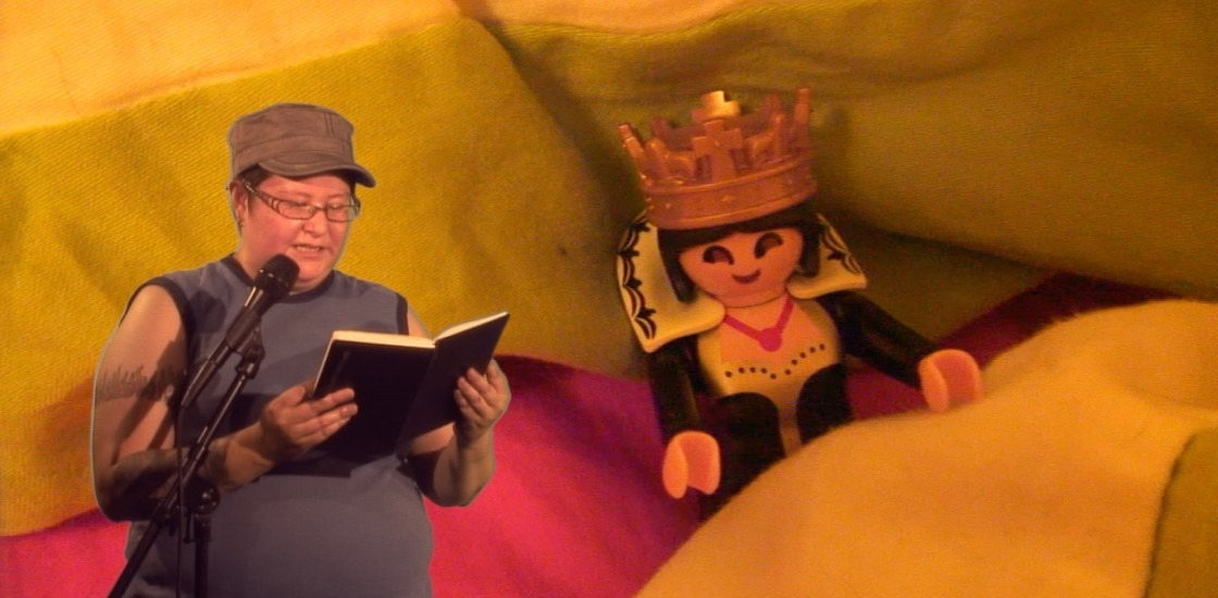 Thirza Jean Cuthand reading from a book on left of image with background of lego human with crown on
