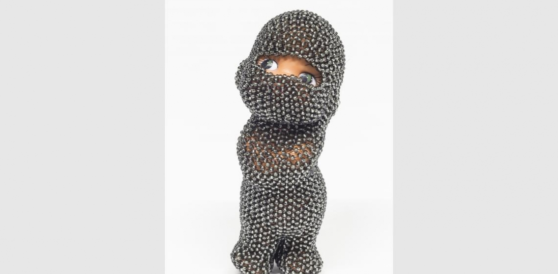 Image of a small doll covered in beadwork