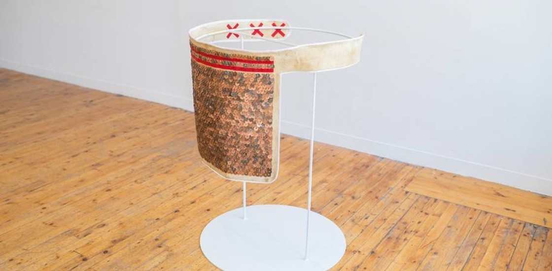 copper sequins sewn on fabric and red stitching on a white metal stand
