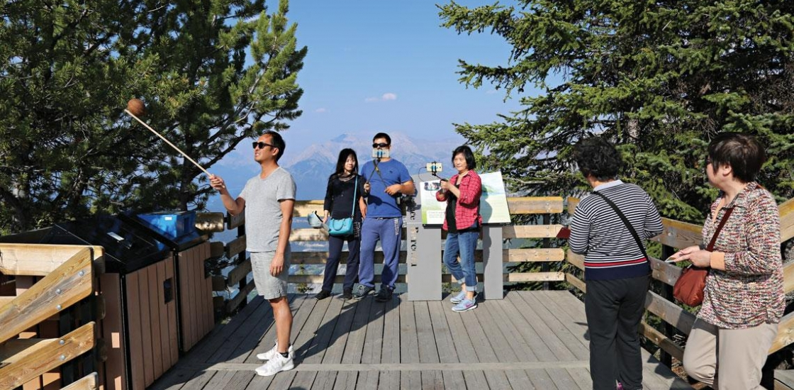 Man taking selfie using a selfie stick with others in the background on a deck
