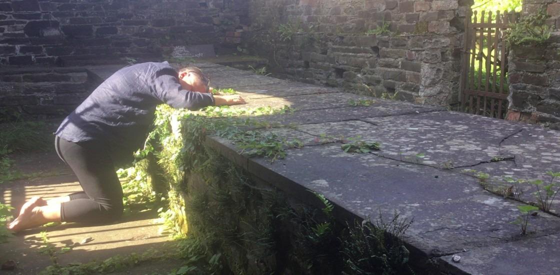 video still of artist bent over rack wall