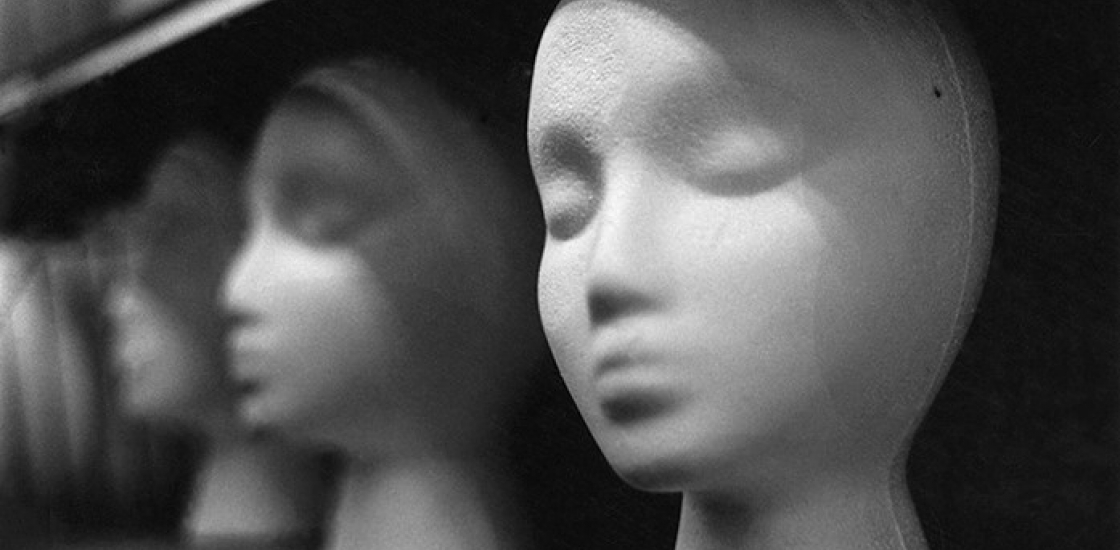 Black and White photo of mannequin heads on a shelf