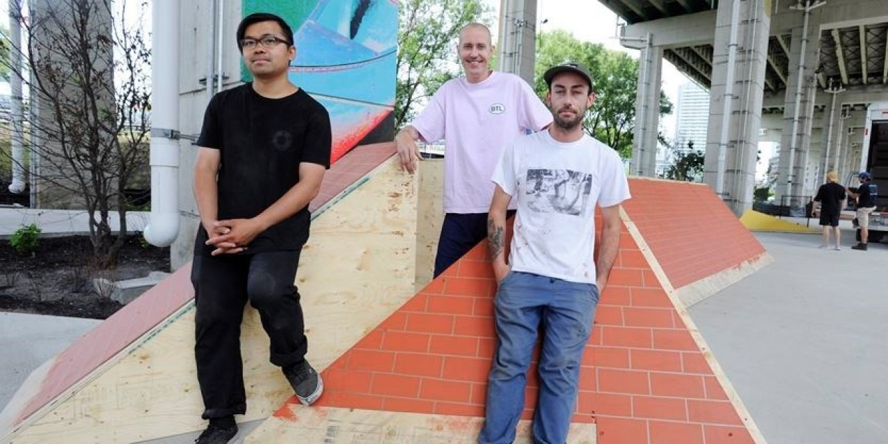 Photograph of Immony Men, West Loates and Josh Singal posing in front of skate ramps at The Bentway.