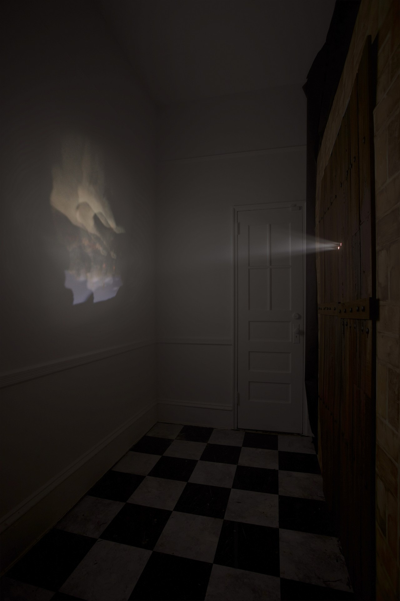 A photo illustration: in a dark room, a projection comes from two small holes in a double door and plays on the wall