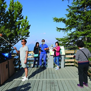 Photo of people standing on a scenic lookout deck, one with a selfie stick