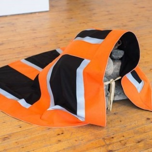 orange cape with black and grey squares wrapped around stone