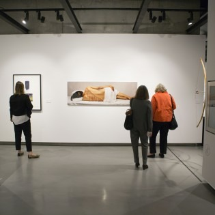 Three people looking at works in a gallery