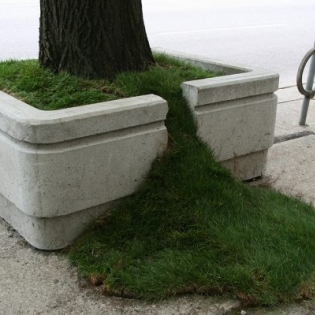 street planter box with grass spilling out a crack in its side