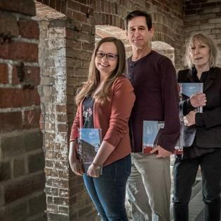 photo of three people in brick hallway