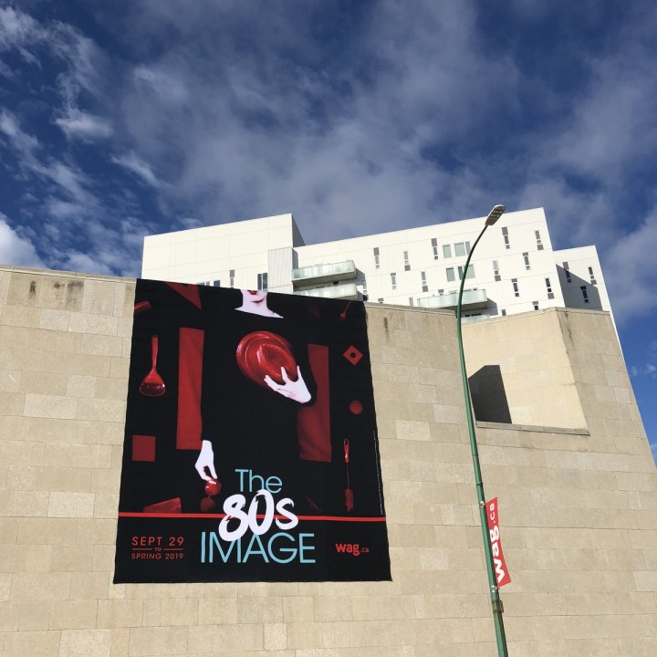 photo banner on the outside of the gallery, woman in black with red additions