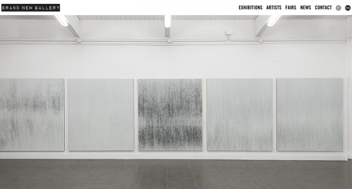 grey artworks on white gallery wall