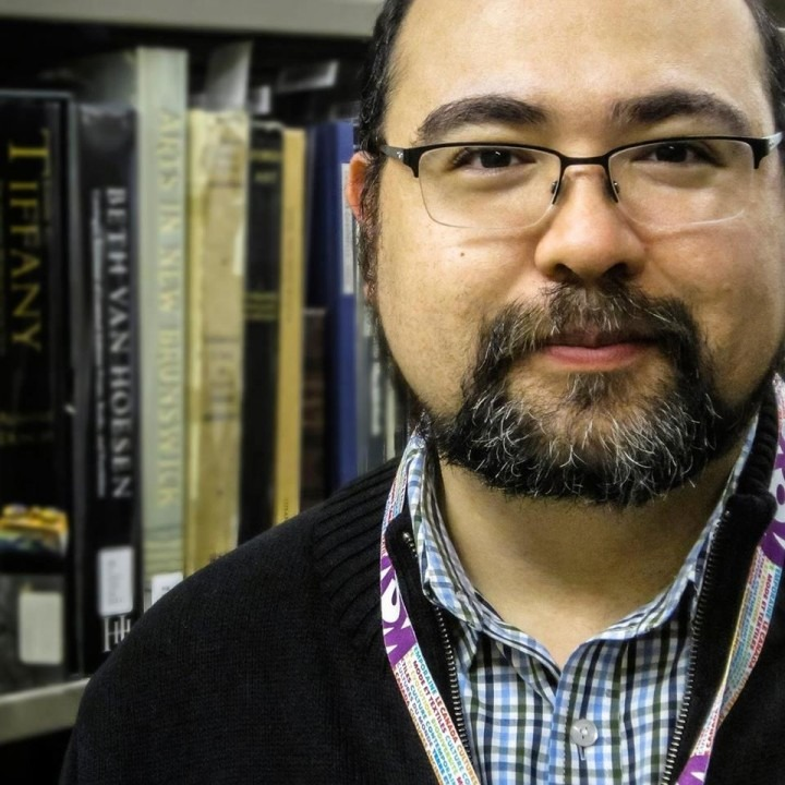 Max Dionisio bespectacled and smiling in front of a book case