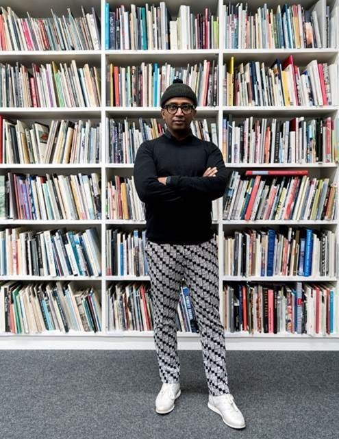photo of the artist in front of a wall of books