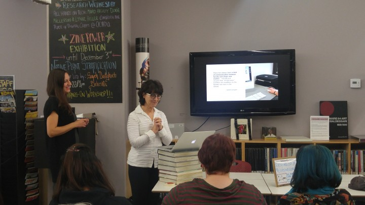 Photograph of Lynne Heller and Dorie Millerson speaking about their research to faculty and students at OCAD U