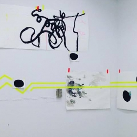 A series of paintings and illustrations hung on a wall with tape, with bright yellow lines intersecting several of the pieces