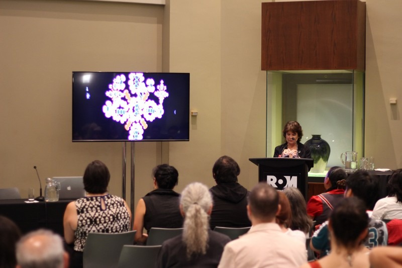 Professor Bonnie Devine behind a podium with beaded digital animation on screen next to her