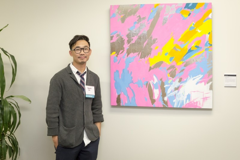 Artist Daniel Wu standing next to his abstract painting with pinks and yellows