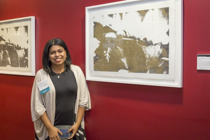 Artist Arruniva Mohendran standing next to her art hung on a red wall