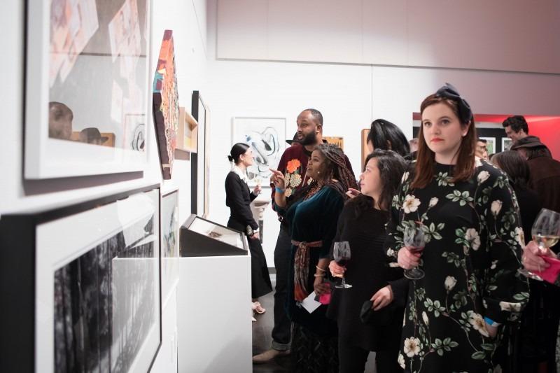 woman looking at artwork on a wall