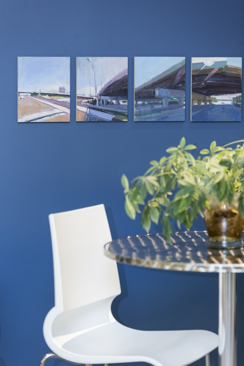 Four paintings on a blue wall with chair below