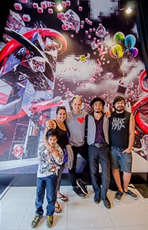 Matthew Del Degan poses with young artists from SKETCH in front of mural created for Virgin Mobile's Queen St West store