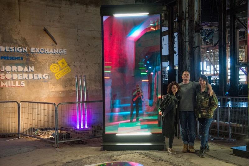 Nina Boccia, Jordan Soderberg Mills, and Tara Akitt in front of Jordan Soderberg Mills' work Anaglyph Mirrors presented by DX at