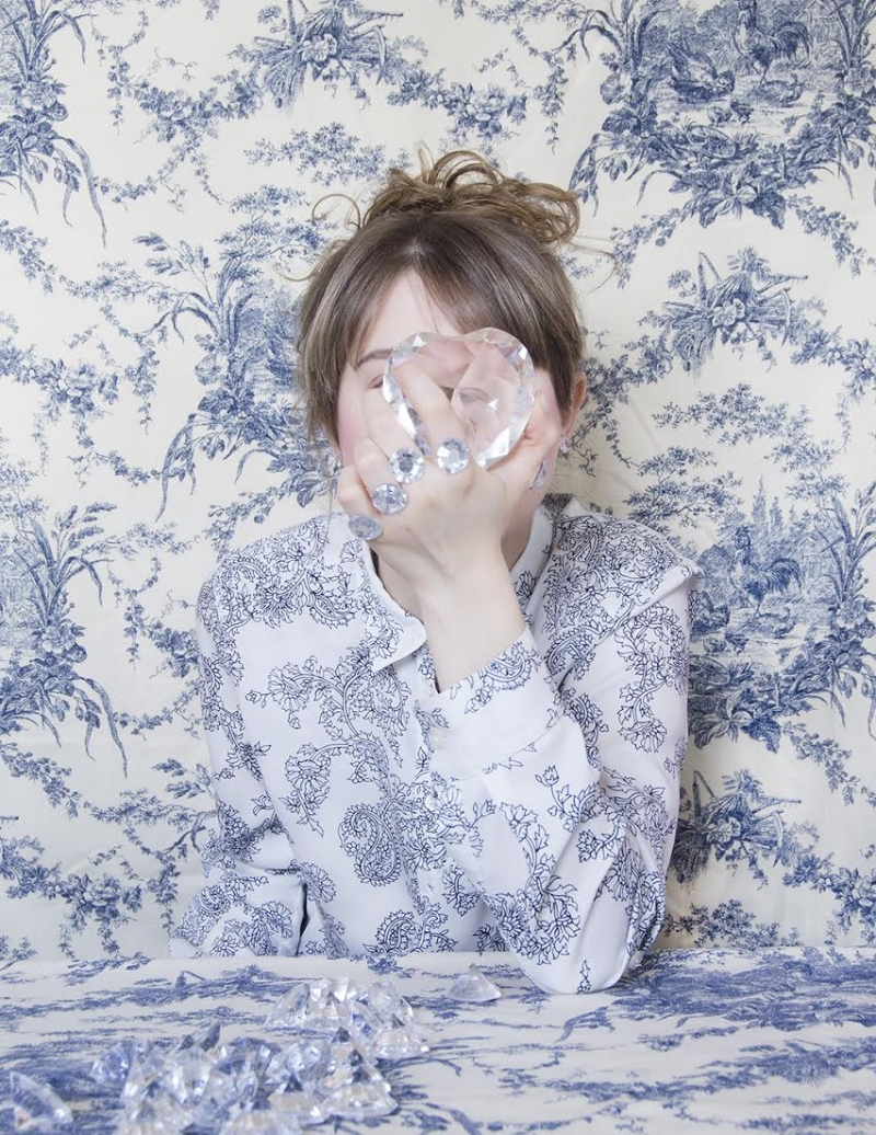 Young woman obscures face with crystal against vintage wallcovering